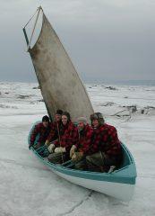 François Lachance, ses fils et un ami, dans le canot qu'ils ont restauré pour reproduire une traversée d'antan, dans le cadre du film De l'eau glacée dans les veines. Photo : Richard Lavoie, 2009
