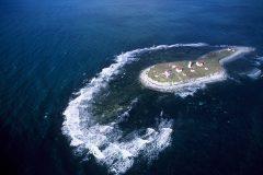 """Autour de l'île aux Perroquets, les récifs sont bordés d'une frange d'écume révélant le haut fond et les difficultés d""""accoster cet îlot rocailleux. Photo de Nelson Boisvert"""