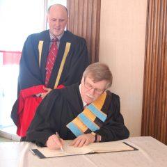 Jean-Pierre Pichette signant le registre officiel de l'Université de Sudbury sous les yeux du recteur, M. Pierre Zundel. Photo : Sarah Noël, Université de Sudbury