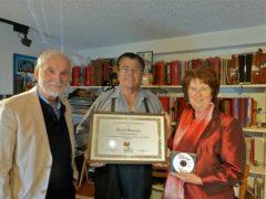 Bernard Genest, à gauche, et Louise Décarie, à droite, remettent un certificat de reconnaissance à Marcel Messervier, facteur d'accordéons, dans le cadre du Programme de valorisation des porteurs de traditions 2015. Photo : Claire Desmeules