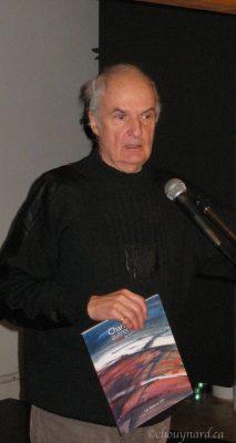Monsieur Cyril Simard montre à l'assemblée le magnifique recueil d'oeuvres picturales sur son pays natal, Charlevoix, qui est paru récemment aux éditions GID. Photo Y. Chouinard
