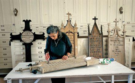 Nicole Bourgault, sous la supervision du Centre de conservation du Québec, travaille à la restauration d'un monument funéraire dans le cadre des efforts entrepris par  la fabrique de Saint-Roch-des-Aulnaies (2004) en faveur de son cimetièread sanctos(ou près des saints, sous l'église).