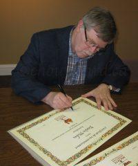 Le président de la Société québécoise d'ethnologie, Jean-Pierre Pichette, signant les certificats de reconnaissances aux artisans acériculteurs. Photo ©chouynard.ca