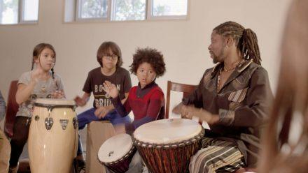 Emmanuel Delly et des jeunes de l'organisme Jeunes musiciens du monde. Image tirée du film Afro-vibes